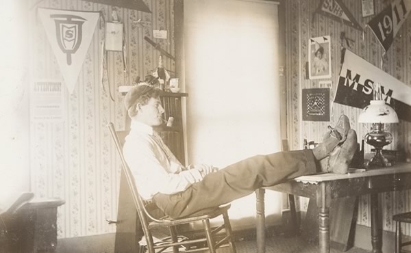 Seated man with feet on desk in student room